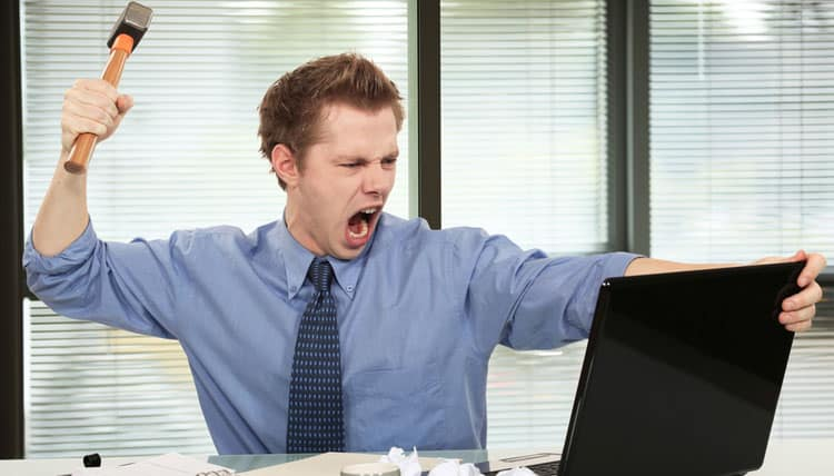 Angry computer user with hammer